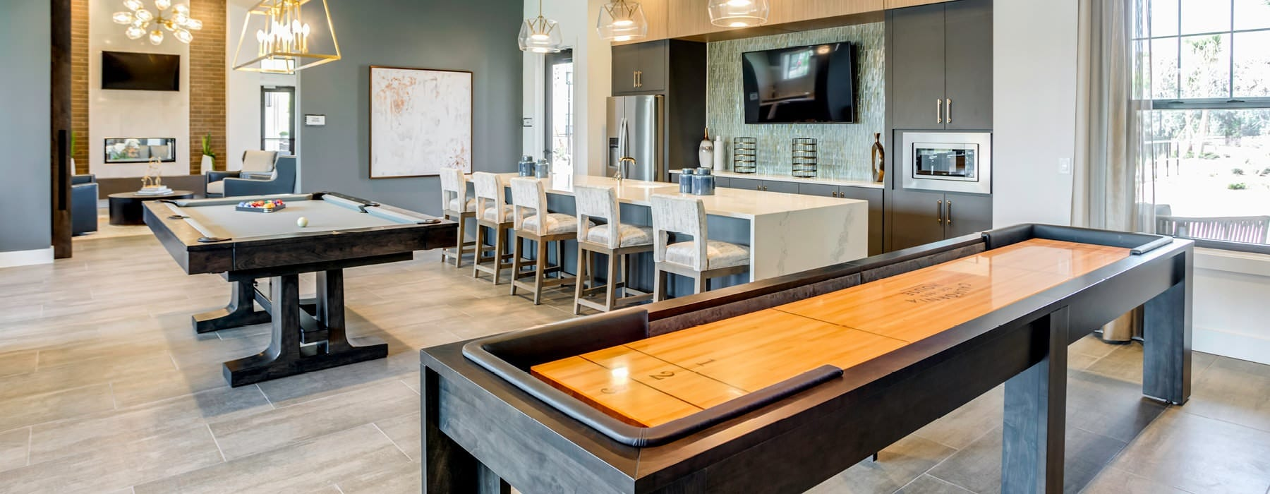 shuffle board and billiards tables in well lit resident lounge with kitchen