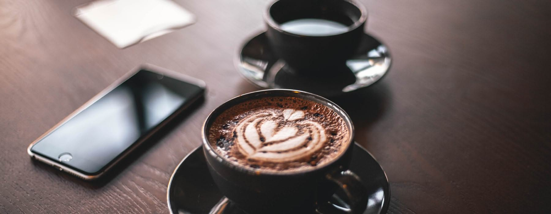 two cups of coffee on table next to cell phone