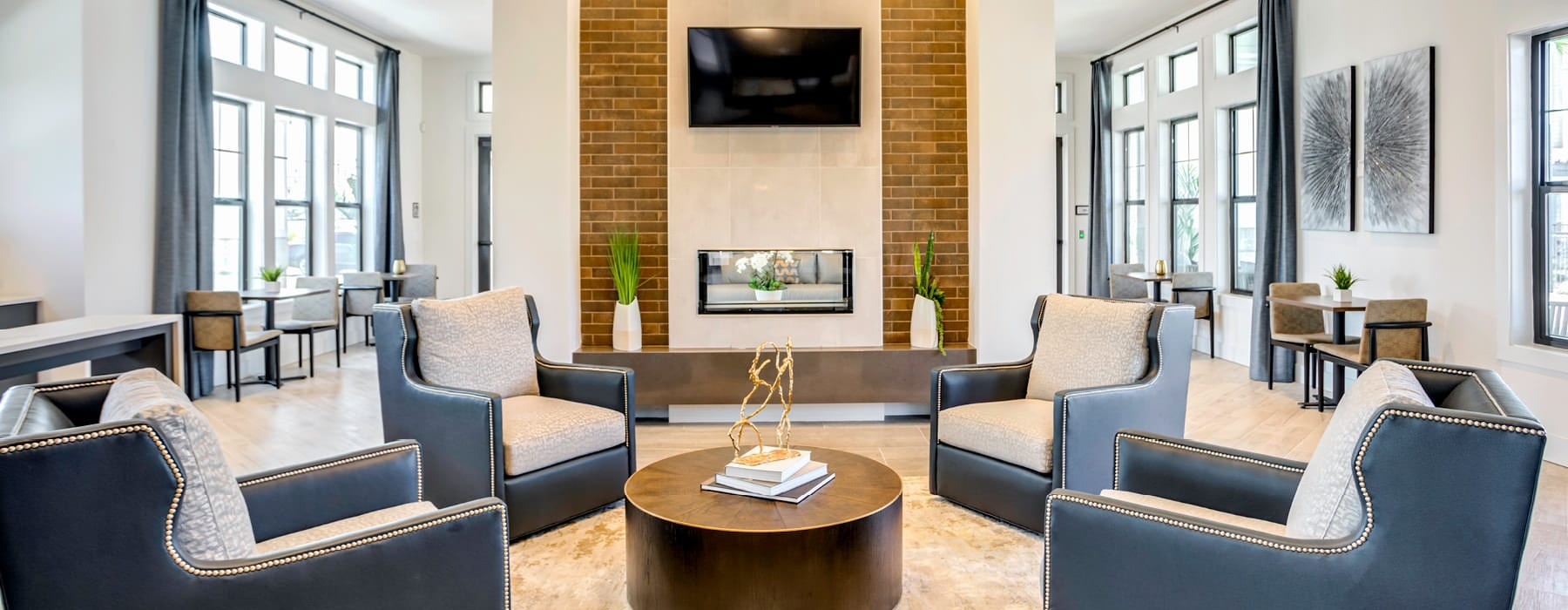 bright community clubhouse lounge area with wall mounted tv